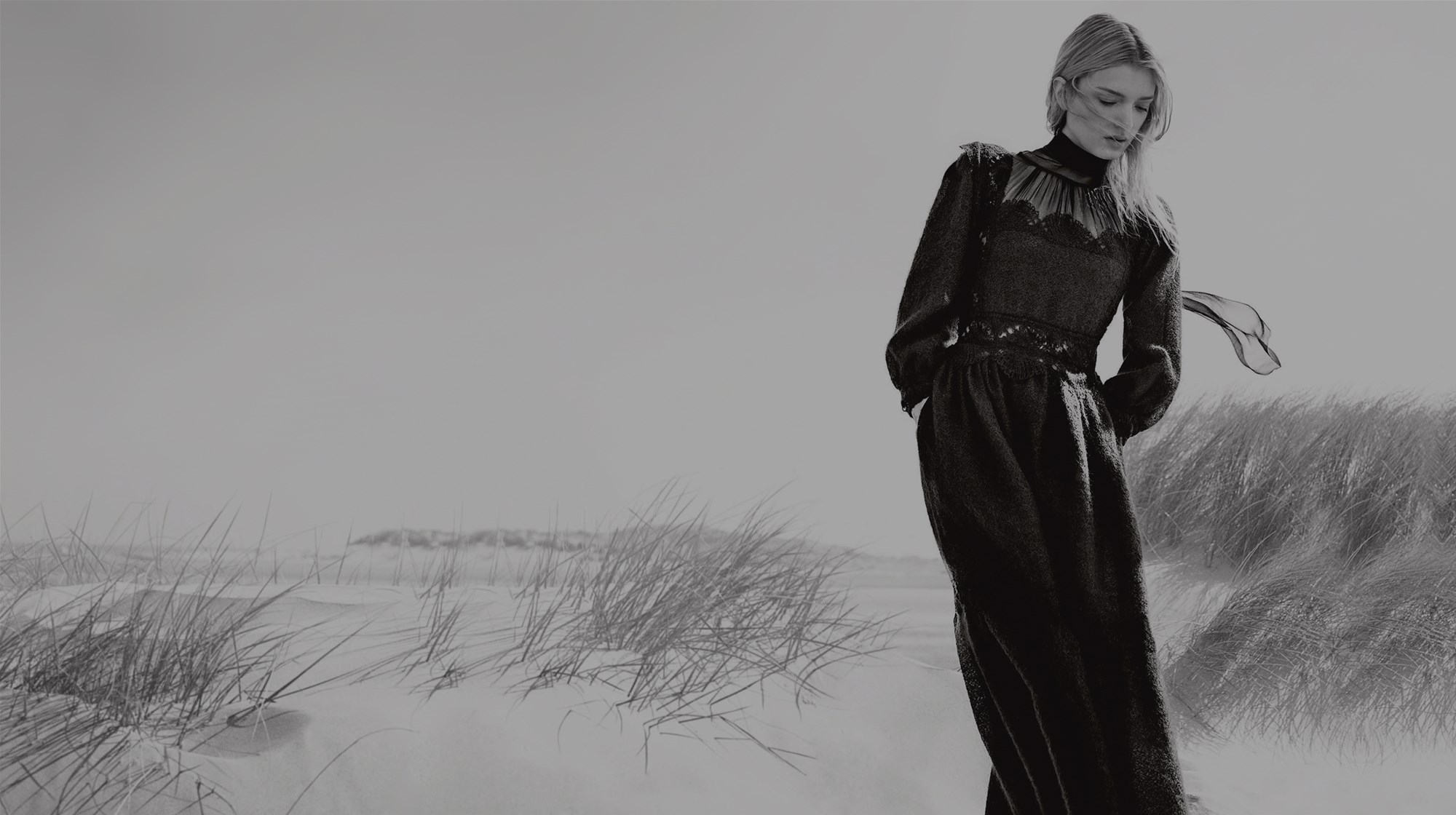 Black and white image of a model posing at a stunning beach location with sand dunes